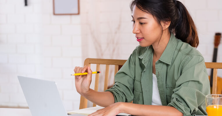 Young female holding pencil as she looks at a laptop screen