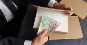 Close-up of man's hands putting Singapore $2 and $5 currency notes inside hardcover book