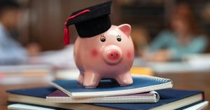 Pink ceramic pig figurine with a black graduate cap on top of notebooks