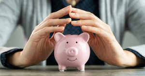 Woman's hands above a pink piggybank on a table