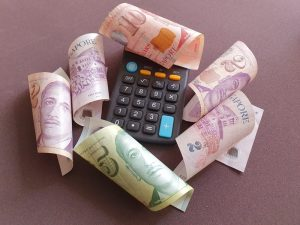 Different denominations of Singapore money and a calculator representing ways to pay off fast cash loans in Singapore